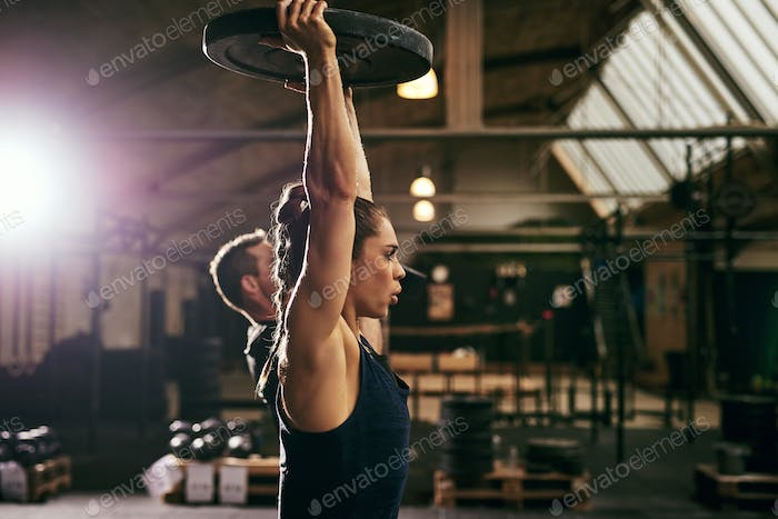 Two young sportive athletes exercising with weights