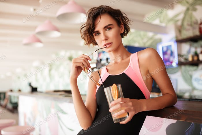 Young beautiful lady standing at bar counter and thoughtfully looking in camera