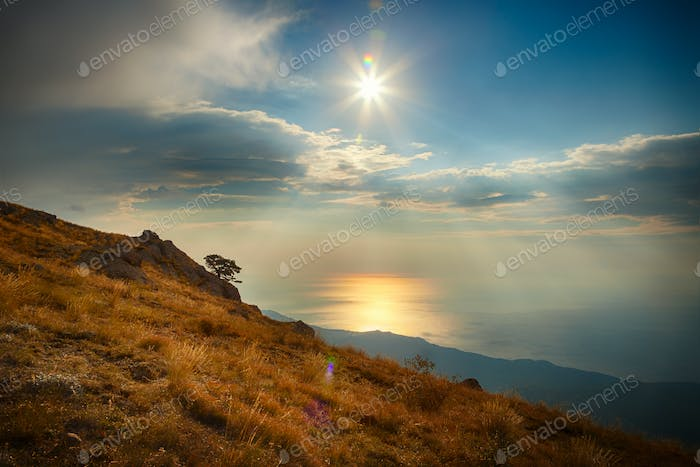 Hillside, sea and sky with clouds and sun
