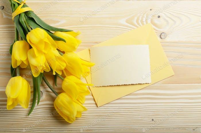 Gelbe Tulpen nahe blanko Grußkarte und Umschlag auf natürlichem W