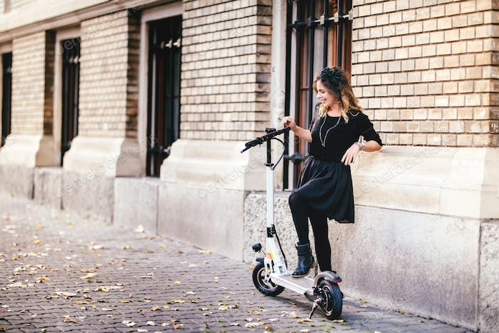 Portrait of attractive woman enjoying electric scooter. Leisure and lifestyle details