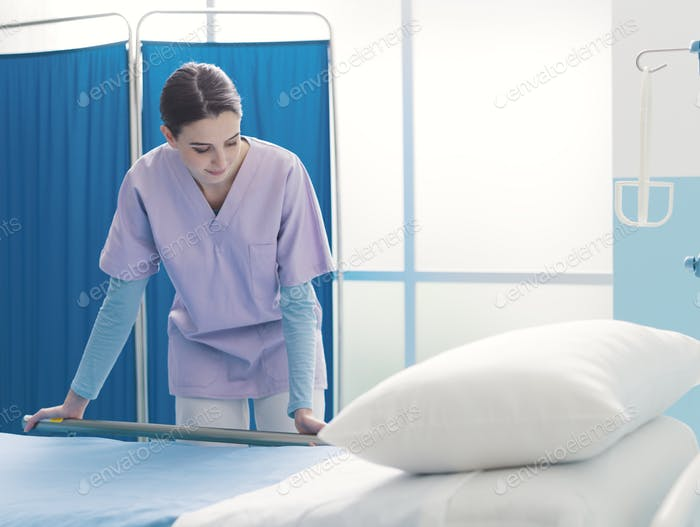 Young trainee nurse working at the hospital and adjusting bed rails
