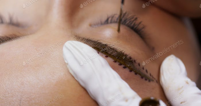Beautician specialist of permanent makeup making brow microblading tattooing make up