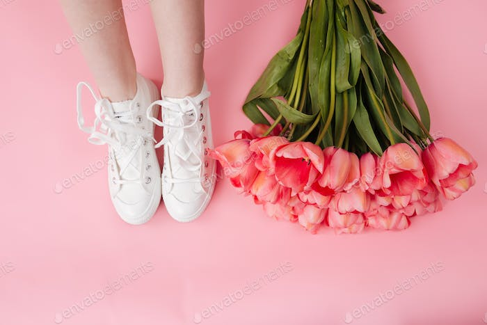 Cropped image of bouquet flowers and legs woman