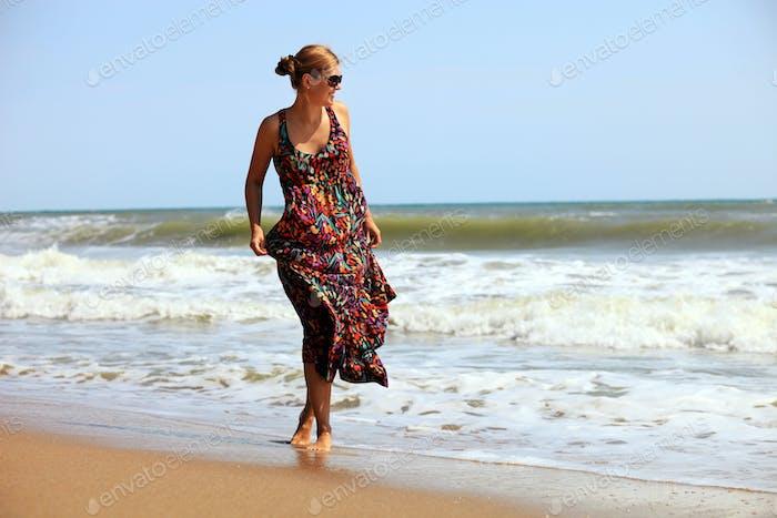 Young Caucasian woman walking along a beach