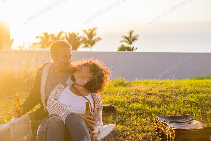 Couple laughing in love during picnic on the meadow for outdoor leisure activity together