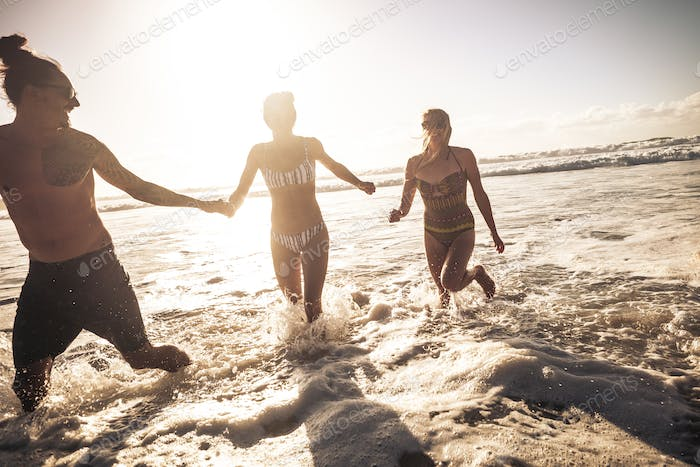 Three young people enjoy summer holiday vacation in friendship playing with sea waves at the beach