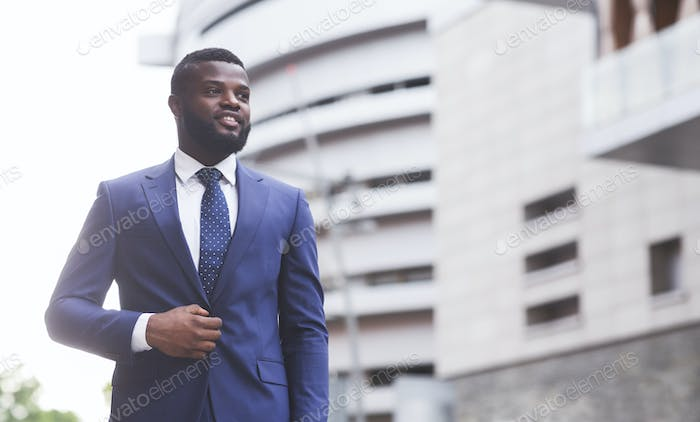 Confident black businessman in stylish suit looking aside outdoors