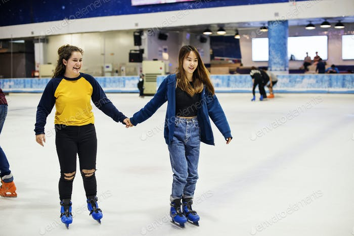Girl friends ice skating on the ice rink together
