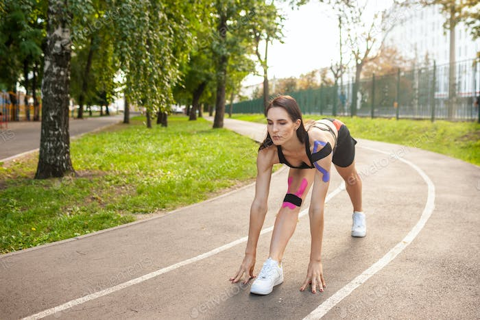 Flexible woman with kinesiotaping training in park.
