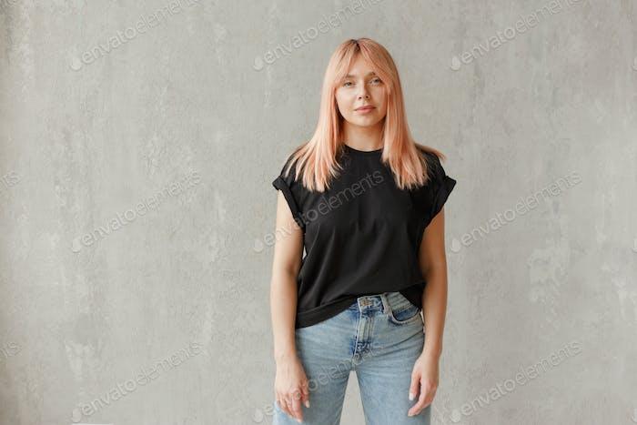 Young girl wearing blank black t-shirt. Concrete wall background. Horizontal