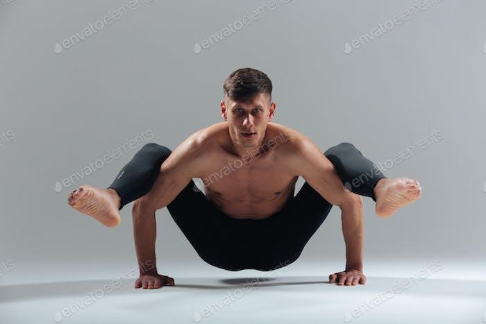 Handsome man doing yoga exercises