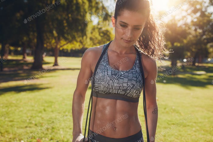 Fit and muscular woman with a skipping rope at the park