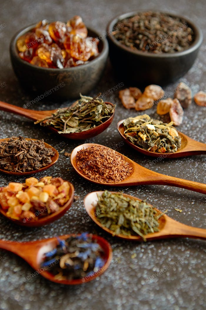 Spoons with different types of dry tea leaves.