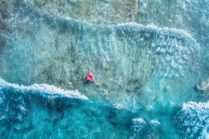 Aerial view of woman in the sea with waves