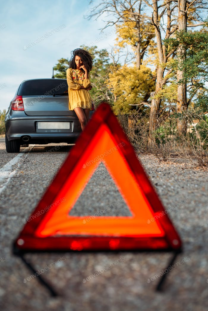 Woman with broken car and triangle