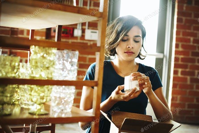 Mujer joven en una tienda, sosteniendo un pequeño objeto de cerámica.