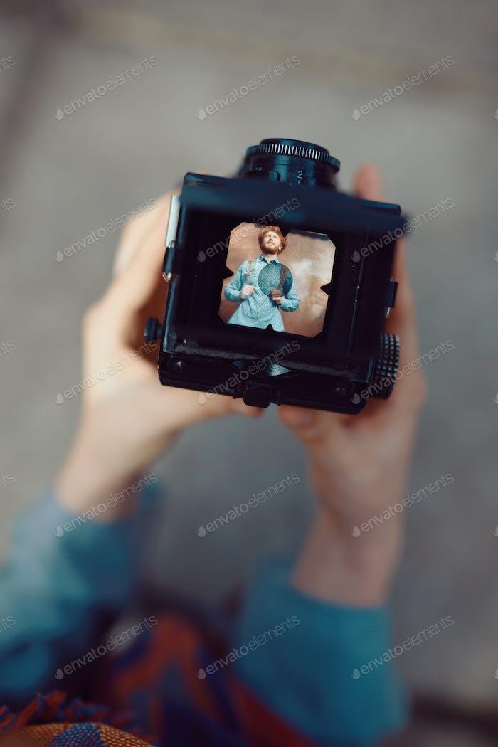 Shooting ein Porträt von hübschen Kerl mit einer Vintage-Kamera