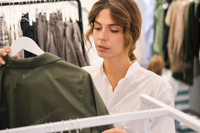 Young confident woman thoughtfully working in showroom with new collection