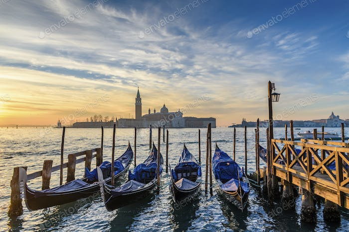 Gondolas moored on a canal in Venice, Italy, at sunrise.