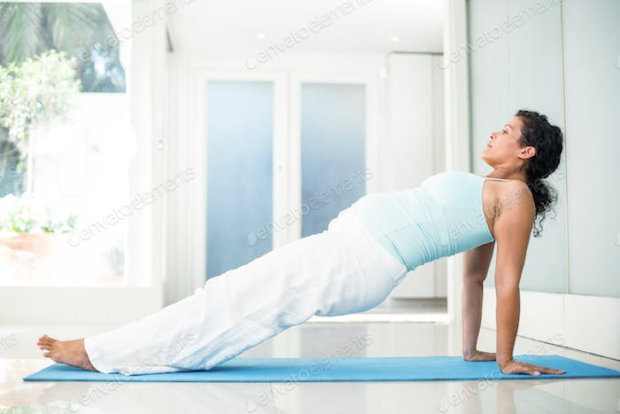 Full length of pregnant woman exercising on mat in a fitness studio