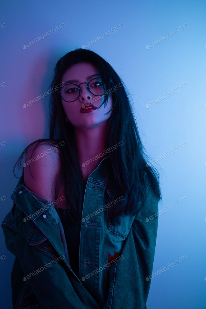 Studio Portrait of Asian Woman Over Urban Neon Lights