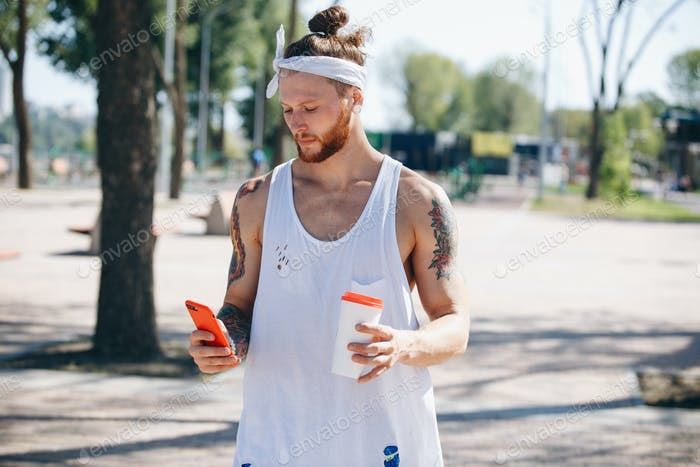 Young man with white headband dressed in a white t-shirt using mobile phone and holds a plastic cup