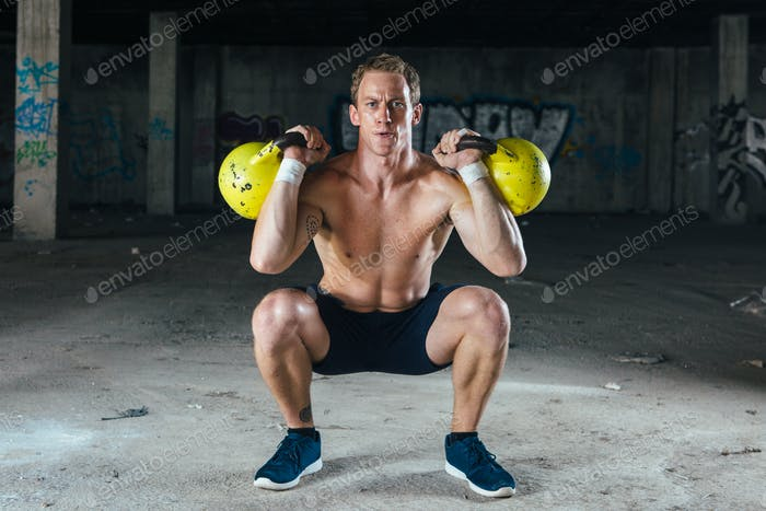 Man lifting dumbbells in abandoned building