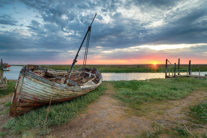 Dramatic sunrise over an old fishing boat on the shore at Thornh