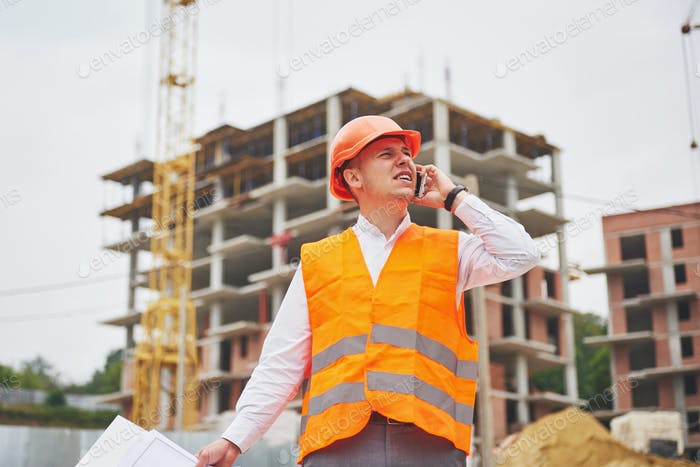Young architect wearing a protective helmet standing on the mountains building outdoor background