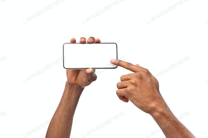 Afro hands holding smartphone with blank screen and pointing at it