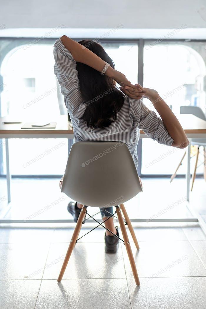 Geschäftsfrau nimmt einen Moment zum Entspannen und Dehnen im Büro. Rückansicht.