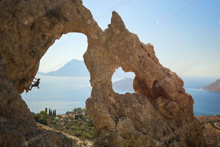Senior female rock climber on a cliff. Kalymnos Island, Greece