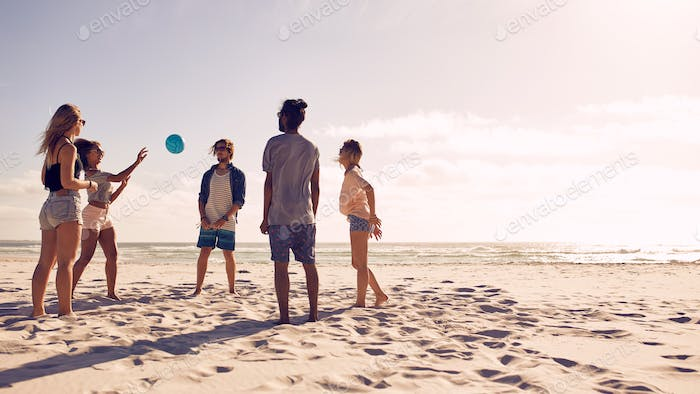 Group of friends playing with ball at beach