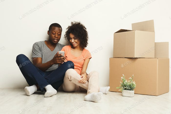 African-american sitting on floor at new appartment