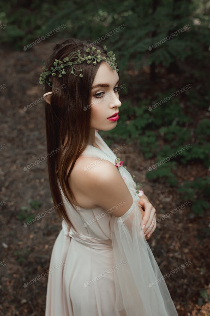 mystic elf in elegant dress and floral wreath in forest