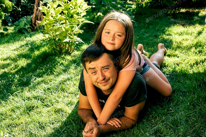 Dad and daughter are lying on the grass in the garden. Happy family holiday concept