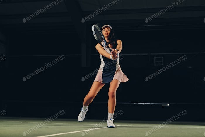 Female tennis player in a jump on a tennis court.