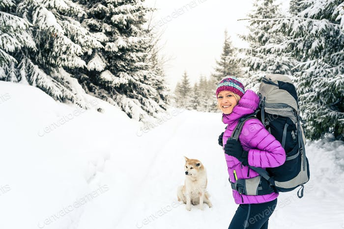 Happy girl hiking in winter forest with dog