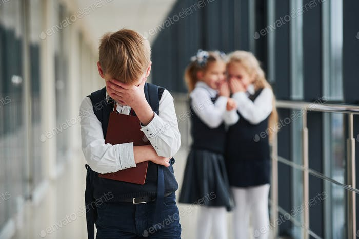 Little boy gets bullied. Conception of harassment. School kids in uniform together in corridor