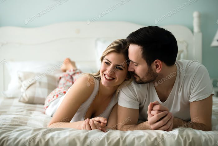 Couple in love wearing pajamas lying in bed