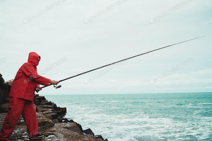 Alter Mann, der im Meer angelt.