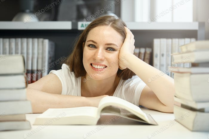 Caucasian female student in a good humor trying to find required information on History, studying a
