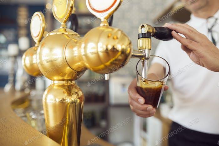 Barman versant de la bière dans un verre à bière