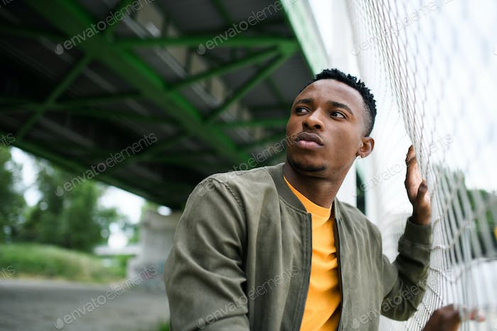 Frustrated young black man behind net outdoors in city, black lives matter concept