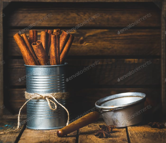 Cinnamon sticks in can tied with rope, anise and sieve