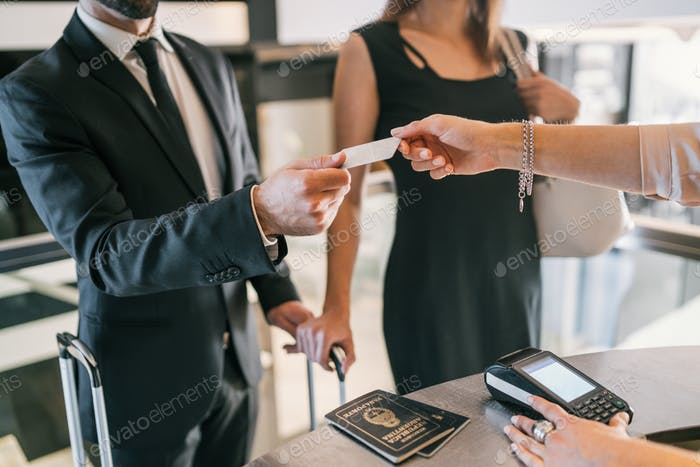 Business people makes card payment at check-in at reception.
