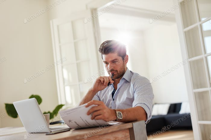 Man at home office with laptop and reading documents