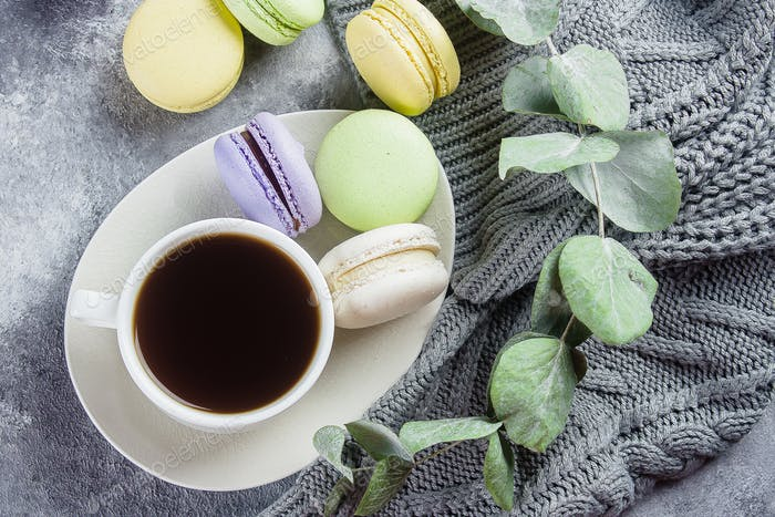 Cozy Morning Home Concept. Delicious pastel macarons with cream and coffee cup, gray sweater