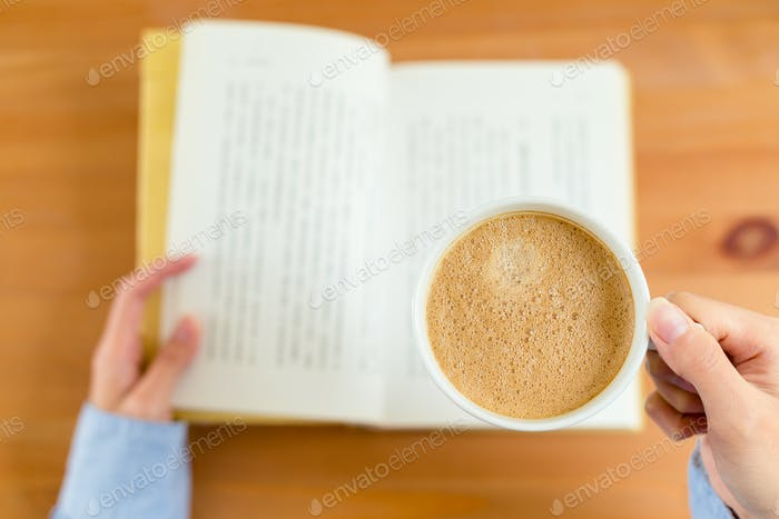 Top view of woman reading book and enjoy her coffee
